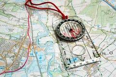 Compas d'Orienteering sur une carte Photographie stock libre de droits