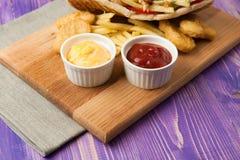 Compas gyroscopiques et fritures et pépites sur un conseil en bois avec deux tasses de sauce sur la table Image stock