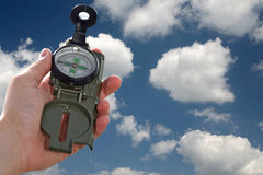 Compass. In the hand with the clouds background Royalty Free Stock Image