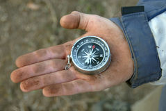 Compass. A very dirty hand holds a compass stock images