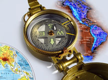 Compass. Close view of a compass next to a global map royalty free stock image