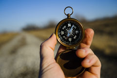 Compass. Person on a gravel road using a compass to find direction Royalty Free Stock Image