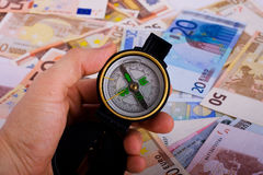 Compass. A compass placed on a lot of money Stock Image