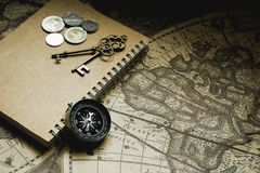 Compass, antique keys and notebook on blur vintage world map, journey concept, copy space. Compass, antique keys, coins and notebook on blur vintage world map Royalty Free Stock Photos