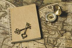 Compass, antique keys and notebook on blur vintage world map, journey concept, copy space Royalty Free Stock Photo