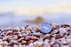 Compass on the beach, small stones, text space. Compass path travel adventure concept target route symbol instrument conceptual navigation explore marketing stock photography