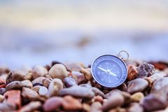 Compass on the beach, small stones, text space. Compass path travel adventure concept target route symbol instrument conceptual navigation explore marketing stock images