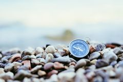 Compass on the beach, small stones, text space. Compass path travel adventure concept target route symbol instrument conceptual navigation explore marketing royalty free stock image