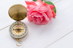 Compass with beautiful pink rose on a white wooden background Stock Photos