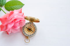 Compass with beautiful pink rose on a white wooden background Royalty Free Stock Photo