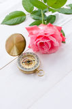 Compass with beautiful pink rose on a white wooden background Stock Image