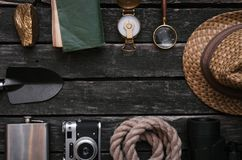 Adventurer. Traveler. Explorer background with copy space. Compass, binoculars, film photo camera, loupe, handgun, diary book, shovel, rope, hat and gold ore on royalty free stock photo
