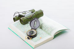 Compass and binoculars on map Stock Photography