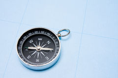 Compass on blue paper background. Royalty Free Stock Image