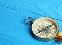 Compass on blue wooden background. Royalty Free Stock Photo