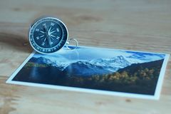Compass on blur photograph of popular toustist destination background, China traveling concept. Compass on blur colorful photograph of popular toustist Royalty Free Stock Photos