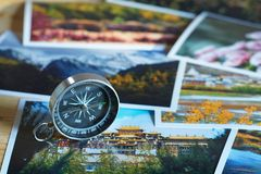 Compass on blur photograph of popular toustist destination background, China traveling concept. Compass on blur colorful photograph of popular toustist Royalty Free Stock Image
