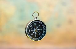 Compass on a blurry background with a vintage world map Stock Photos