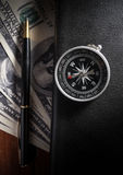 Compass on book with pen and money. Royalty Free Stock Photo