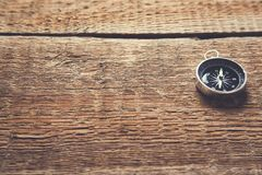 Compass on brown vintage wooden table background royalty free stock photo