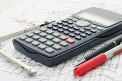 Compass , calculator and pens. Compass, electronic calculator and pens on top of blueprints Stock Image