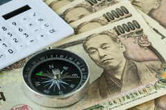 Compass and calculator on pile of japanese yen banknotes as fina Royalty Free Stock Photography