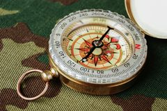 Compass on a camouflage. Background stock photography