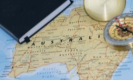 Compass on a close up map pointing at Australia and planning a travel destination with traveller notes in the photo. Compass on a map pointing at Australia and Royalty Free Stock Photography