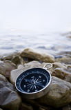 Compass on the coast. Compass with pebbles and water Royalty Free Stock Image
