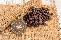 Compass and coffee beans on burlap sack on wooden background Royalty Free Stock Photos