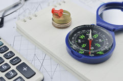 Compass coin notebook calculator and glasses on business graph Royalty Free Stock Photography