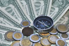 Compass and coins laying on a pile of on dollar bills stock photo