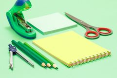 Compass, color pencils, notebook, note paper, stapler and scissors on green background. Back to school concept. School supplies. Shallow depth of field stock images