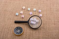 Colorful letter cubes behind a magnifying glass. Compass and colorful letter cubes behind a magnifying glass Stock Photo