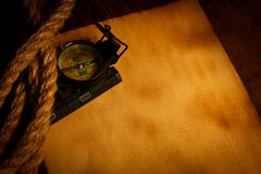 Compass and cordage on old paper. Compass and cordage on empty old paper, wooden background Royalty Free Stock Photos