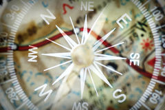 Compass. Detail of a magnetic compass on the background of the blurred image of the geographical map Royalty Free Stock Photography