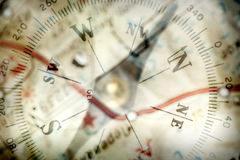 Compass. Detail of a magnetic compass on the background of the blurred image of the geographical map Royalty Free Stock Photos