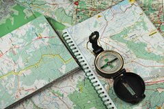 Compass on the detailed maps. Black, military compass on the detailed maps as a background stock images