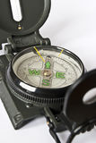 Compass close up. Close up of a compass with green arrows on white background Stock Image