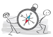 Compass - directional reference. Two stick figures carry a compass Stock Photos