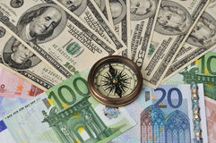 Compass on dollars and euro. Compass on money - dollars and euro Royalty Free Stock Images
