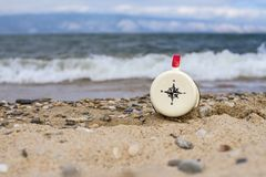 Compass on an enameled mug pointing to the south on the sand of Lake Baikal on the island of Olkhon during the tide of a wave. Royalty Free Stock Image