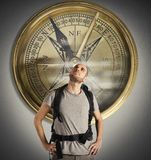 Compass of explorer. Explorer with uncertain expression with big compass Stock Photos