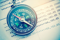 Compass financial concept. Compass and papers about financial issues Royalty Free Stock Photo
