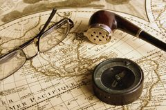 Compass glasses pipe. Eye glasses, compass and tobacco pipe on the ancient map during rest of an navigator (colors are with sepia effect Royalty Free Stock Images