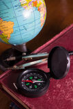 Compass with globe on antique book. Stock Photo