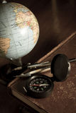 Compass with globe on antique book,still life. Royalty Free Stock Photo