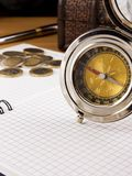 Compass, gold coin and pen on notebook Stock Images