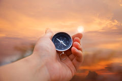 Compass in hand. Hand holding the compass in sunset Stock Photo