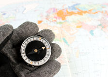 Compass on hand. Hand in hiking glove holding compass with map of the world in background stock image